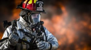 Firefighter standing in front of a fire