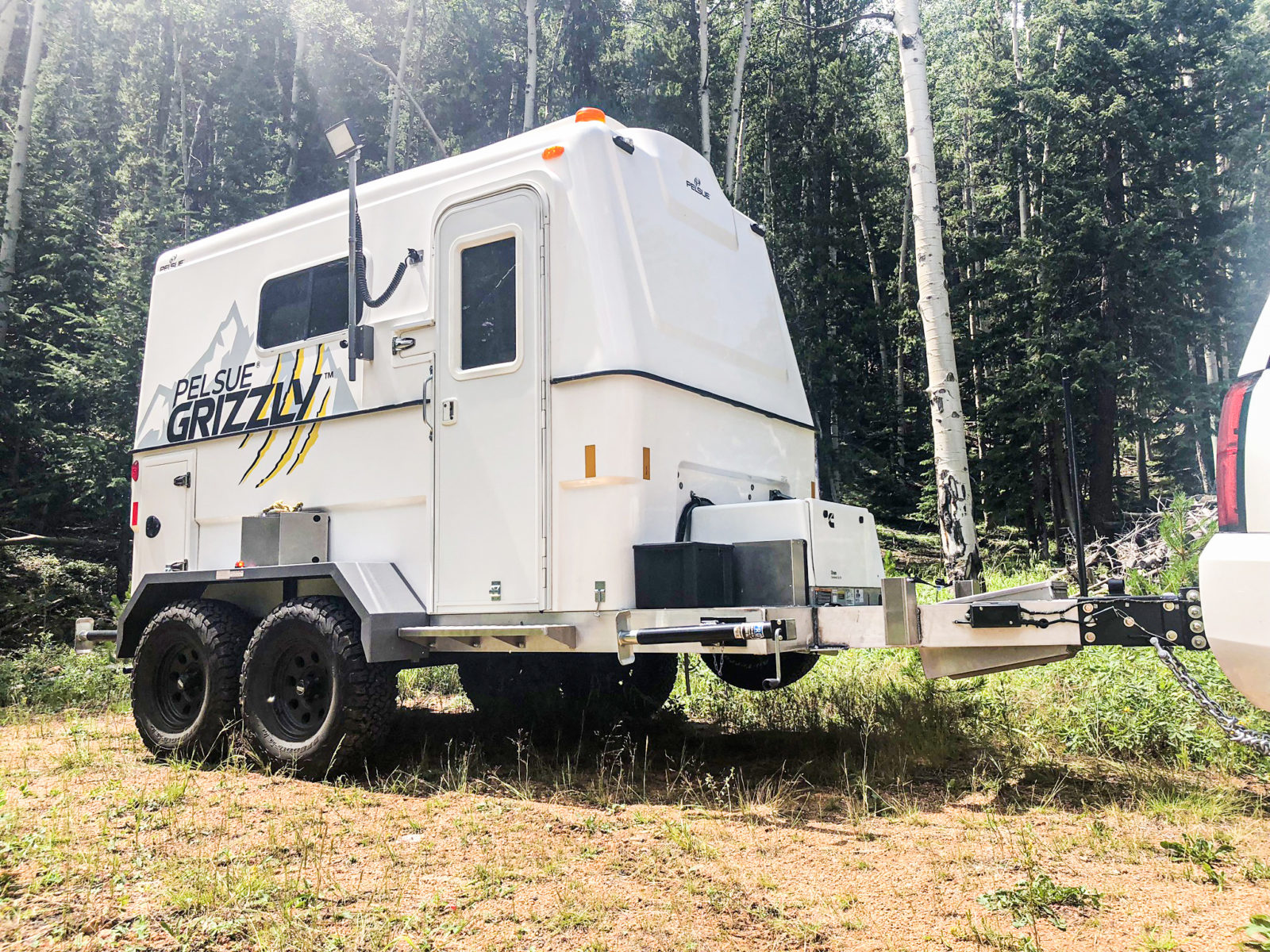 The Pelsue FiberLite Grizzle fiber splicing trailer parked in a mountain forest.