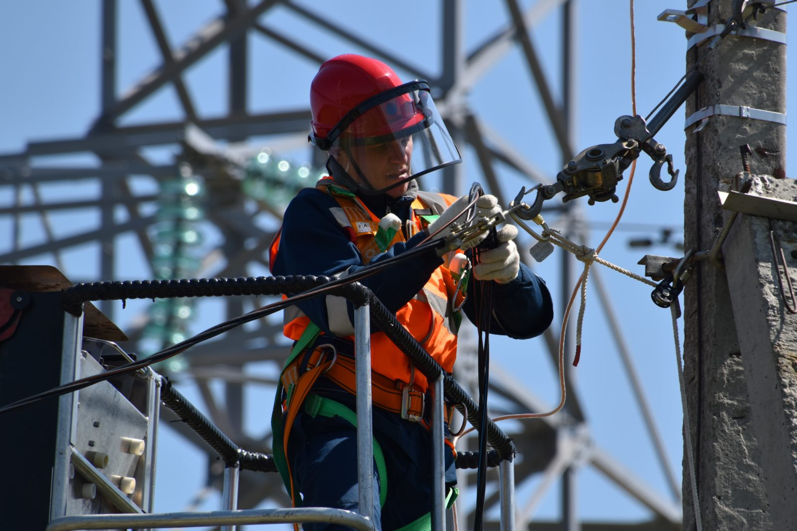 Electrician working high up on a power line wearing proper hard hat, gloves, safety vest, and harness.